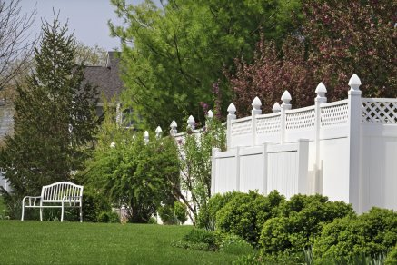 Beautiful new vinyl fence with nice landscaping in a backyard setting