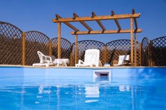 Garden Pergola viewed from sparkling fresh swimming pool. Summer garden furniture.